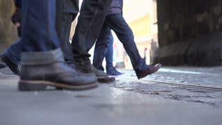 Feet stepping on street to cross in slow motion.