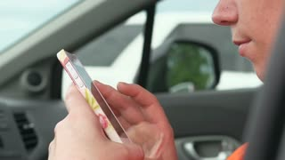 Female browsing smart phone sitting in car