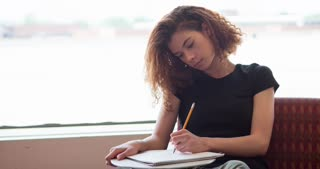 Female college student writing in notepad with pencil 4k
