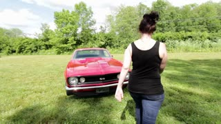 Female getting into classic muscle car