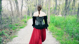 Female in Renaissance clothing walking down path in woods 4k