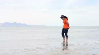 Female kicking around water on shore