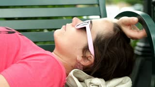 Female laying on park bench with sunglasses