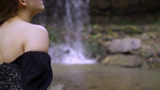 Female looking in awe while standing at waterfall 4k