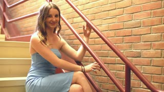 Female model sitting against stairwell rail