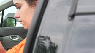 Female on cell phone in car slider shot