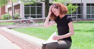 Female on college campus writing in notebook outdoors 4k