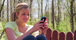 Female outside on cell phone smiling 4k