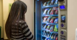 Female picking out snack selection at vending machine 4k.