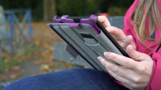 Female reading digital book while outdoors 4k