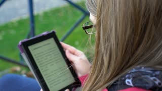 Female reading ebook on tablet over the shoulder view 4k