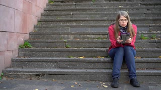 Female reading ebook outdoors sitting on steps 4k