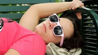 Female relaxing on park bench