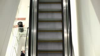 Female riding down escalator