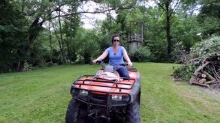 Female riding on four wheeler towards camera