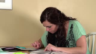 Female sitting at kitchen table budgeting