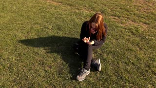 Female sitting in grass using smart phone outdoors 4k