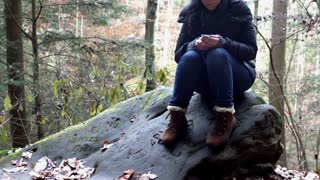 Female sitting in wood texting
