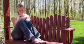 Female sitting on porch swing writing in notebook 4k