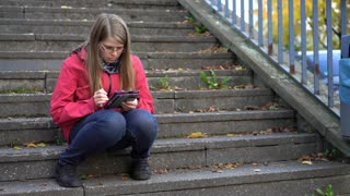 Female sitting on steps outdoors reading ebook 4k