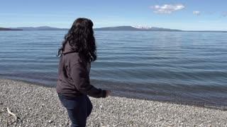 Female skipping rocks in lake