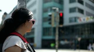 Female standing against traffic light post