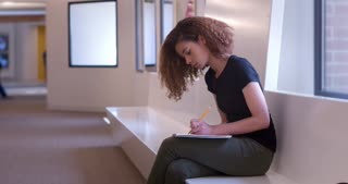 Female student writing notes with pencil into notepad 4k