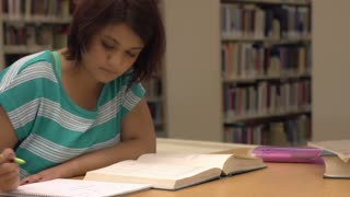 Female taking notes from book in library