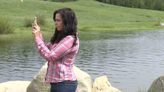 Female taking panoramic picture of lake