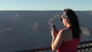 Female taking picture of Grand Canyon