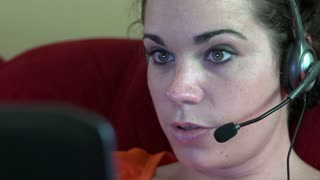 Female telephone receptionist working from laptop