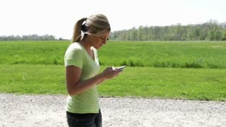 Female texting and walking through nature.