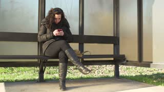 Female texting at bus stop