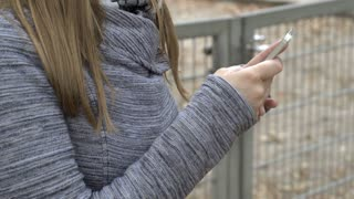 Female texting on cell phone outdoors in park 4k