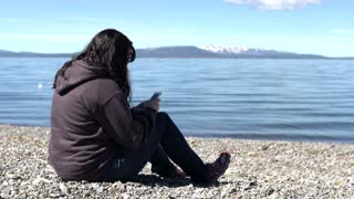 Female texting on lake shore