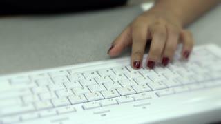 Female typing at white keyboard