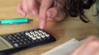Female using calculator at table