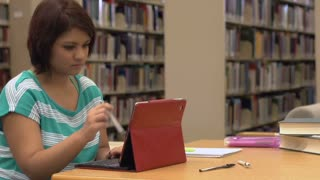 Female using tablet in library