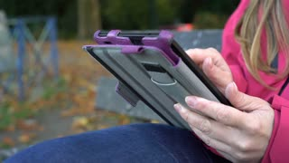 Female using tablet while sitting outdoors in nature 4k