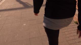 Female walking down city sidewalk 4k
