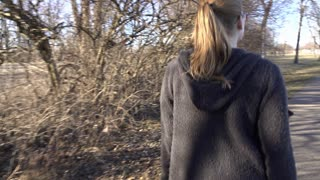 Female walking down path in park steadicam 4k