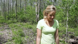 Female walking in woods tracking shot.