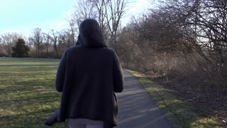 Female walking on park path in the afternoon 4k