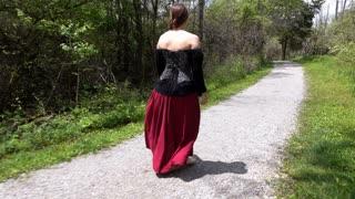 Female wearing renaissance outfit walking through woods 4k