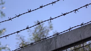 Fence with barbwire protecting from intruders 4k
