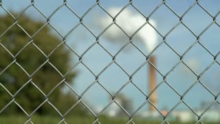 Fence with industrial plant smoke stack in background 4k