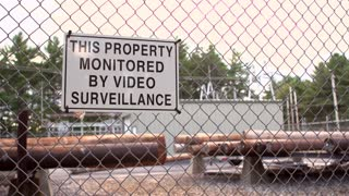 Fenced in property with sign warning people of surveillance