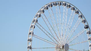 Ferris wheel rotates on blue sky background 4k