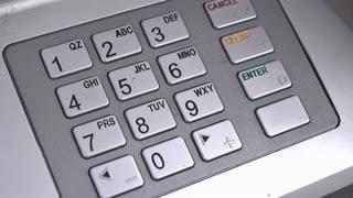 Finger entering secret pin number at ATM 4k