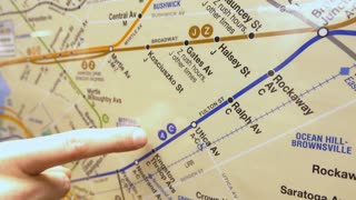 Finger pointing out locations on subway map 4k